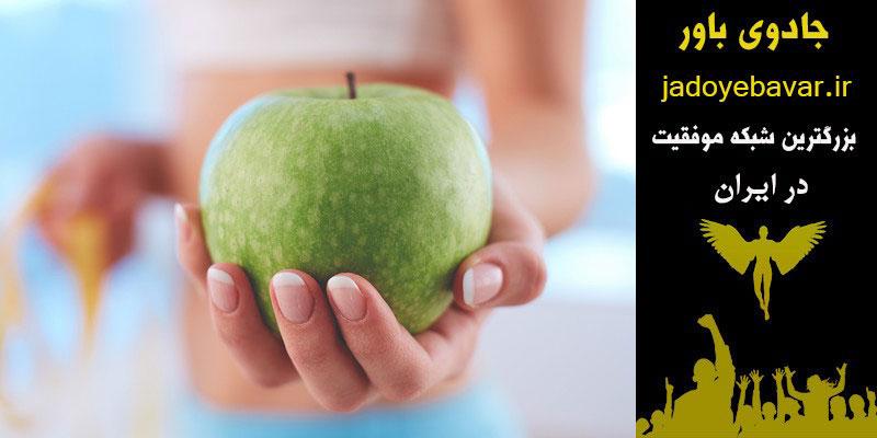 لاغری با قانون جذب ،کاهش وزن با قانون جذب ،عکس یک سیب در دست یک نفر